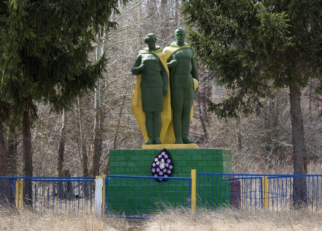 A monument dedicated to villagers killed during World War Two is seen in the abandoned village of Orevichi, in the exclusion zone around the Chernobyl nuclear reactor, southeast of Minsk, April 21, 2015. (Photo by Vasily Fedosenko/Reuters)
