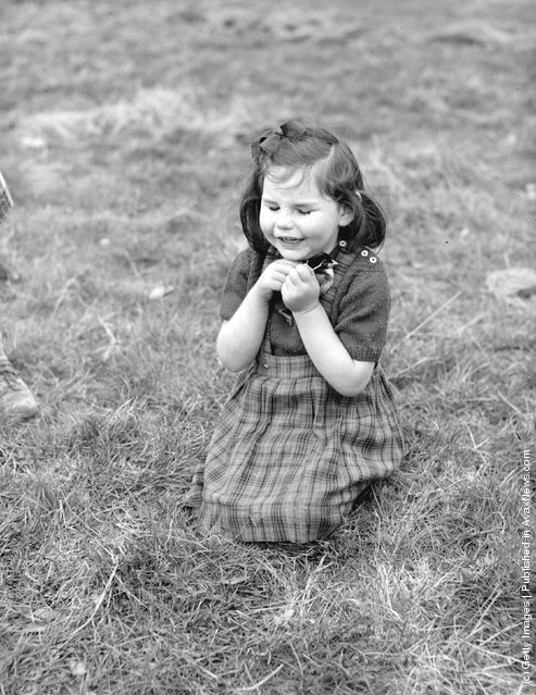 A little blind girl kneels in the grass clutching a baby chick in her hands