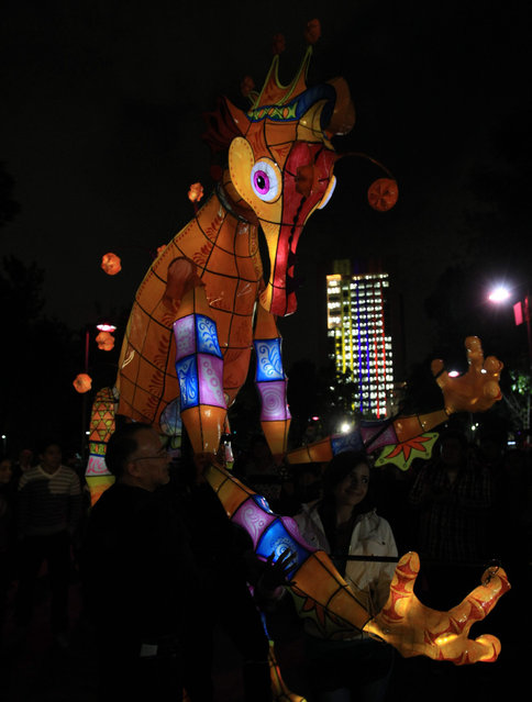 People watch the artistic lighting on a figure near the Fine Arts Palace during the beginning of the International Lights Festival of Mexico (FILUX) in Mexico City, Mexico, 07 May 2015. (Photo by Maruio Guzman/EPA)