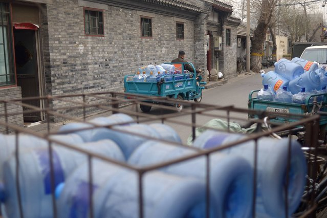 "A courier riding an electric tricycle with barrels of water leaves a shop selling bottled water in an alley in Beijing on March 22, 2016. Environmental watchdog Greenpeace warned on March 22 the world's coal plants are ""deepening"" the global water crisis as the water consumed by them can meet the basic needs of one billion people. (Photo by Wang Zhao/AFP Photo)"