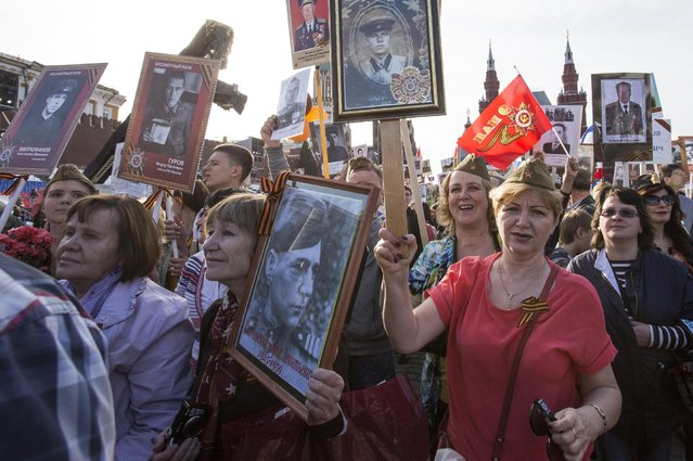 People holding portraits of relatives who fought in World War II march through Red Square in Moscow, Russia, marking the 70th anniversary of the defeat of the Nazis in World War II, Saturday, May 9, 2015. (Photo by Denis Tyrin/AP Photo)