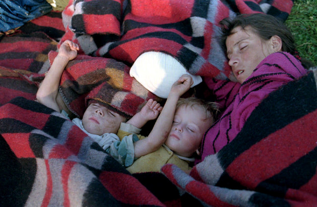 A mother and two children from Srebrenica sleep during the dawn hours on the ground outside the U.N. base at Tuzla airport, July 1995. (Photo by Reuters)
