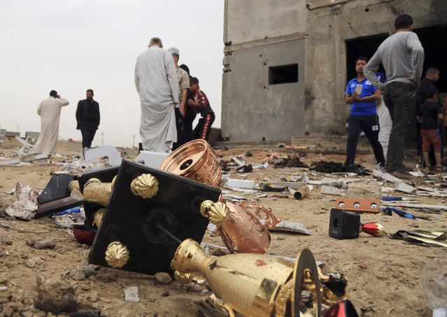 Broken cups lie on the ground as people inspect the aftermath of a suicide bombing at a soccer field in Iskandariya, 25 miles (about 40 kilometers) south of Baghdad, Iraq, Saturday, March 26, 2016. A suicide bomber killed and wounded dozens in an attack on a crowd gathered at the soccer stadium on Friday. (Photo by Karim Kadim/AP Photo)