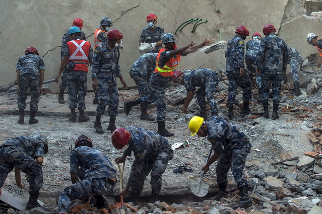 Nepalese military personnel remove debris in search of survivors after a fresh 7.3 earthquake struck, in Kathmandu, Nepal, May 12, 2015. (Photo by Athit Perawongmetha/Reuters)