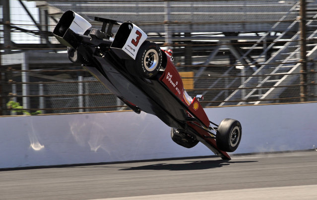 The car driven by Helio Castroneves, of Brazil, flips after hitting the wall in the first turn during practice for the Indianapolis 500 auto race at Indianapolis Motor Speedway in Indianapolis, Wednesday, May 13, 2015.  (Photo by Dick Darlington/AP Photo)
