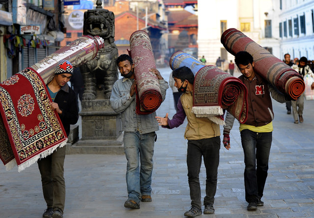 Nepalese street vendors carry carpets as they walk through Durbar Square in Kathmandu on March 5, 2014. Home to the palaces of Malla and Shah kings who ruled over the city, Durbar Square is listed as a UNESCO world heritage site. (Photo by Prakash Mathema/AFP Photo)