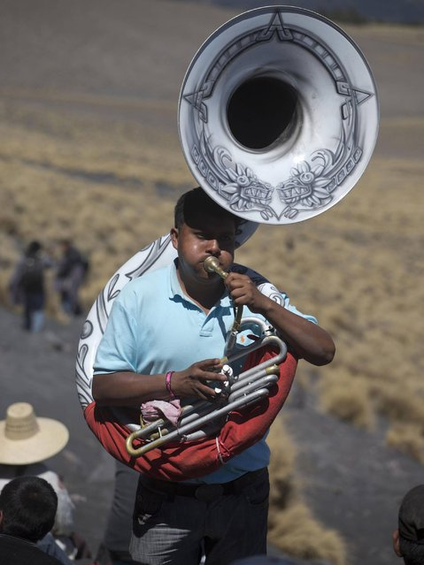 A man plays the tuba during the yearly pilgrimage on the slopes of the Popocatepetl volcano in Mexico. (Photo by Eduardo Verdugo/AP Photo)