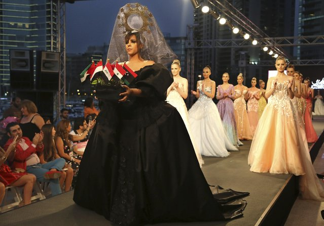 A model, foreground, holds small flags of Arab nations as she and other models display creations by the Emirati designer Mona al-Mansouri of her Spring-Summer 2015 fashion show during the summer fashion week at Saint George Yacht Club in Beirut, Lebanon, Tuesday, May 19, 2015. (Photo by Hussein Malla/AP Photo)
