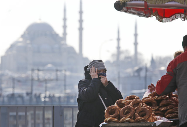 In this Thursday, April 4, 2019 photo, a woman, backdropped by the Suleymaniye mosque, buys simit, a pretzel-like snack, in Istanbul. The mood among opposition supporters in Turkey's biggest city is one of jubilation but also worry – fear that their win in Istanbul's mayoral race could be overturned in a recount taking place after the ruling party challenged the election results. (Photo by Lefteris Pitarakis/AP Photo)