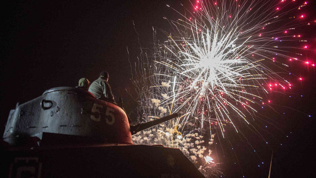 People on a tank watch fireworks in Arromanches in Normandy region of France, Thursday, June 6, 2019. World leaders and veterans gathered Thursday in France to mark the 75th anniversary of the D-Day landings. (Photo by Rafael Yaghobzadeh/AP Photo)