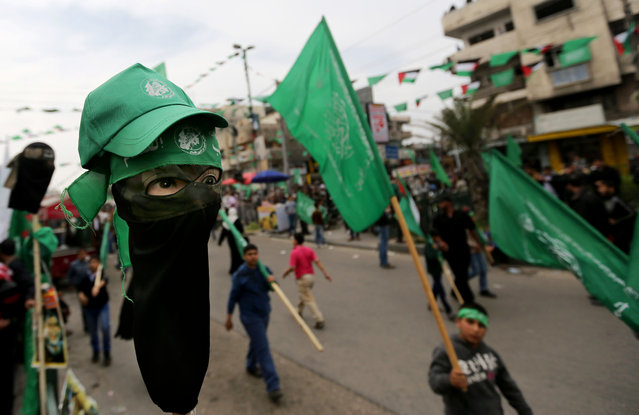 Hamas bandanas are displayed for sale on a mannequins head, left, as tens of thousands of Hamas supporters attend a rally to commemorate the 10-year anniversary of the assassination of the group's spiritual leader in an Israeli airstrike, in Gaza City, Sunday, March 23, 2014. (Photo by Hatem Moussa/AP Photo)