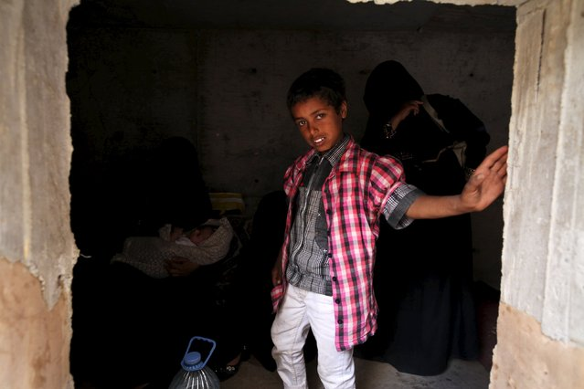 A boy stands next to his mother's inside an underground water tunnel with other displaced Yemeni families, after they were forced to flee their home due to ongoing air-strikes carried out by the Saudi-led coalition in Sanaa May 2, 2015. (Photo by Mohamed al-Sayaghi/Reuters)