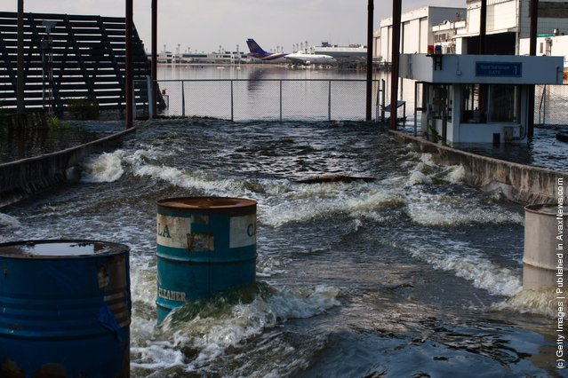 Floodwaters flow at a gate of the closed Don Muang Airport in Bangkok, Thailand