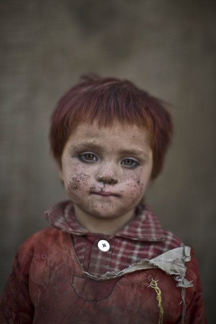 In this Friday, January 24, 2014 photo, Afghan refugee girl, Gul Bibi Shamra, 3, poses for a picture, while playing with other children in a slum on the outskirts of Islamabad, Pakistan. (Photo by Muhammed Muheisen/AP Photo)