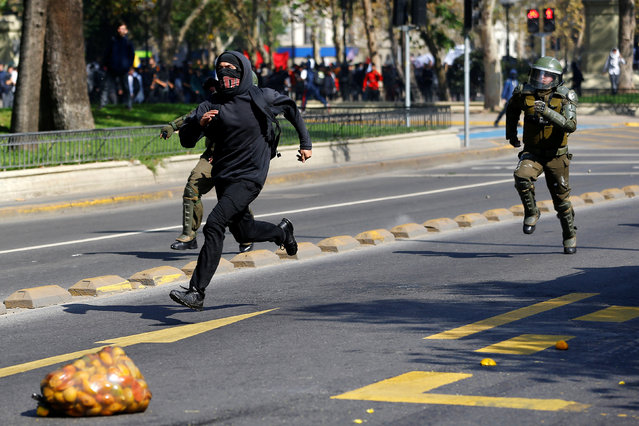 A student protester runs away from riot policemen during a demonstration to demand changes in the education system in Santiago, Chile, April 21, 2016. (Photo by Ivan Alvarado/Reuters)