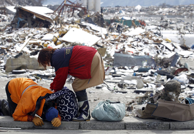 Survivors react after collecting their belongings at their destroyed house in a village hit by an earthquake and tsunami in Otsuchi, northeast Japan March 17, 2011. (Photo by Lee Jae-Won/Reuters)