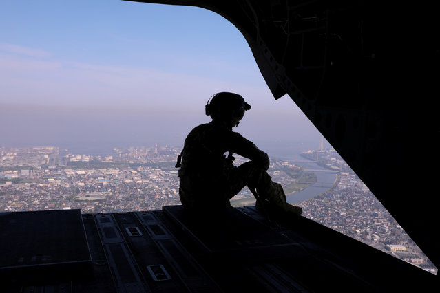 A U.S. Army soldier looks out over Tokyo from the back of a helicopter transporting journalists to cover Japan's Prime Minister Shinzo Abe and U.S. President Donald Trump as they play golf at Mobara Country Club in Mobara, Chiba prefecture, Japan May 26, 2019. (Photo by Jonathan Ernst/Reuters)