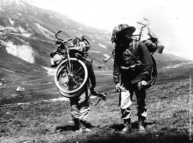 1915: A couple of soldiers from the Italian Rifle Battalion, carrying their bicycles on their backs as they walk up a hill