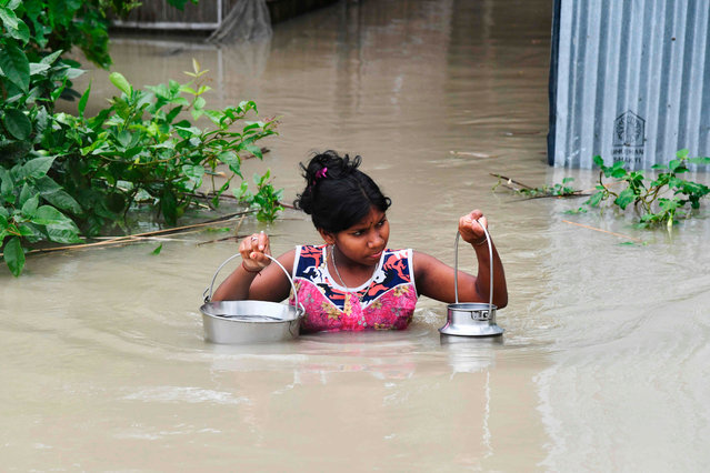 An Indian girl carries drinking water as she wades through flood waters at Pabhokathi village in Morigaon district of India's Assam state on July 15, 2019. Floods and landslides caused by the annual deluge have wreaked deadly havoc from the Himalayan foothills to low-lying camps housing Rohingya refugees, with officials warning tolls could rise as they scramble to reach affected communities. (Photo by Biju Boro/AFP Photo)