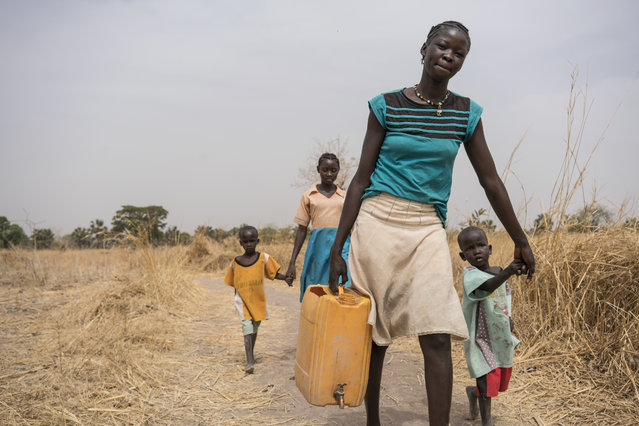 In this photo taken Sunday, March 12, 2017, a girl Abuk walks home with her brothers and friends after collecting clean water from a water point four kilometers away from her home, in Aweil, in South Sudan. As World Water Day approaches on March 22, more than 5 million people in South Sudan, do not have access to safe, clean water, compounding the problems of famine and civil war, according to the UNICEF. (Photo by Mackenzie Knowles-Coursin/UNICEF via AP Photo)