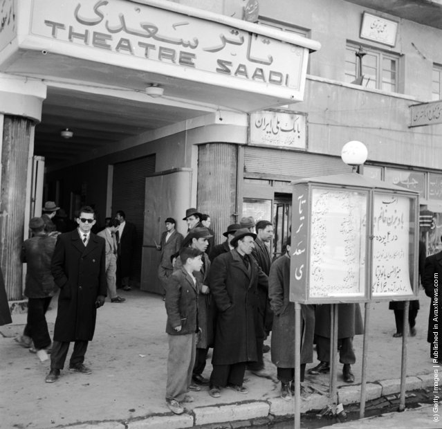 1950:  The exterior of Tehran's Theatre Saadi where a group of people study a billboard