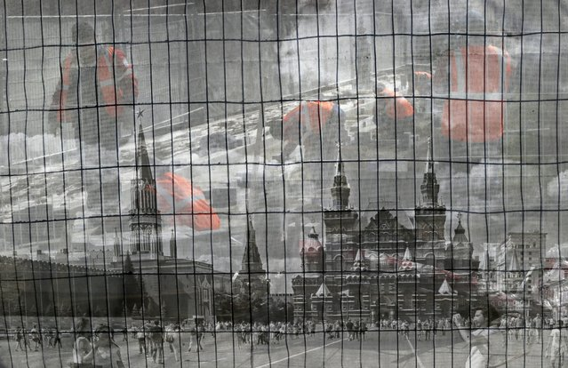 Municipal workers from Asian republics are seen through a fence with picture of the Red Square during their work on landscaping around the Kremlin in Moscow, Russia, 10 April 2014. (Photo by Yuri Kochetkov/EPA)
