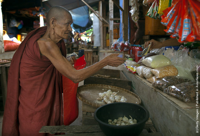An elderly monk visits a market to collect donations of food and money