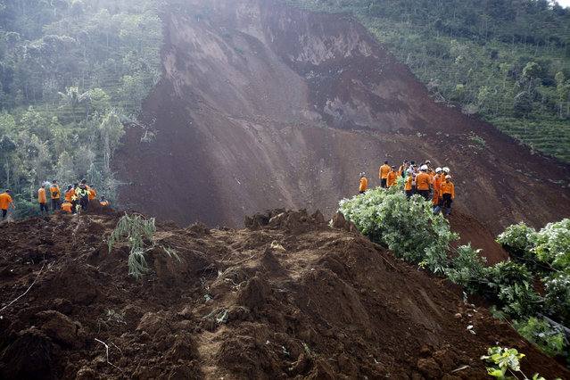 Indonesian rescuers search for victims at Banaran village which is hit by a landslide in Ponorogo, Indonesia, 02 April 2017. At least 28 people are missing and hundreds were evacuated to safer residential areas after a rain-triggered landslide hit a village in Ponorogo, East Java. (Photo by Ali Lutfi/EPA)