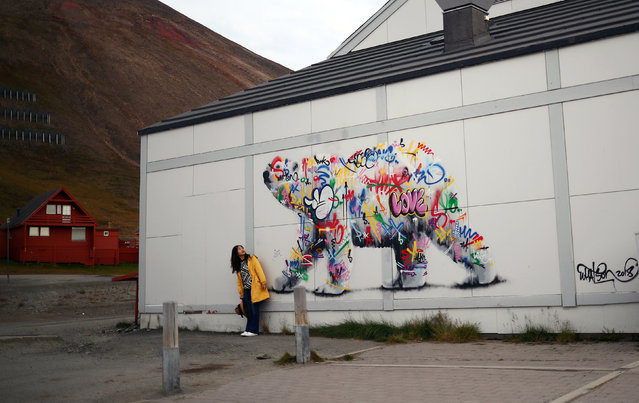 A woman poses next to a polar bear mural in the town of Longyearbyen in Svalbard, Norway, August 6, 2019. (Photo by Hannah McKay/Reuters)