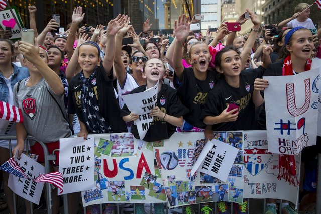 """Fans of the U.S. women's soccer team cheer during the ticker tape parade to celebrate their World Cup final win over Japan on Sunday, in New York, July 10, 2015. The World Cup winning U.S. women's football team rolled up New York City's """"Canyon of Heroes"""" on Friday, with a blizzard of confetti swirling overhead in the first ticker-tape parade honouring a women's sports team. (Photo by Andrew Kelly/Reuters)"""