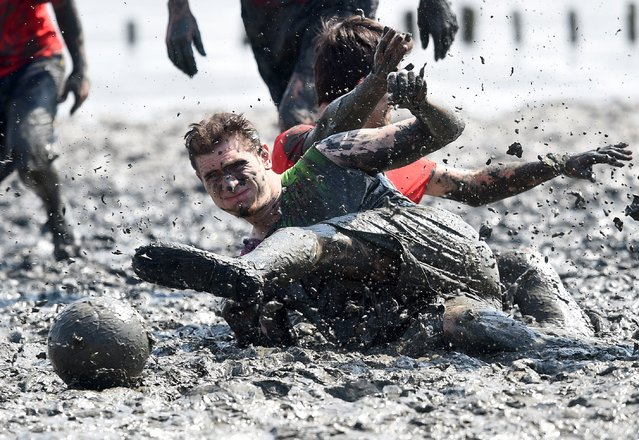 """Players fight for the ball during a soccer match at the so called """"Wattoluempiade"""" (Mud Olympics) in Brunsbuettel at the North Sea, July 11, 2015. (Photo by Fabian Bimmer/Reuters)"""