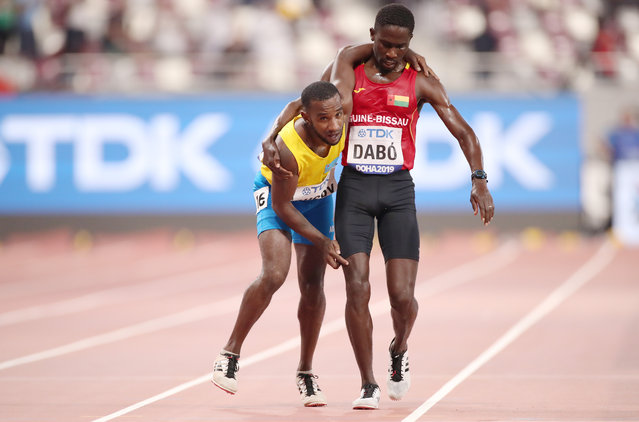 Guinea-Bissau's Braima Suncar Dabo assists Aruba's Jonathan Busby across the line of a men's 5000m heat at the World Athletics Championships in Doha, Qatar, Friday, September 27, 2019. (Photo by Christian Petersen/Getty Images)