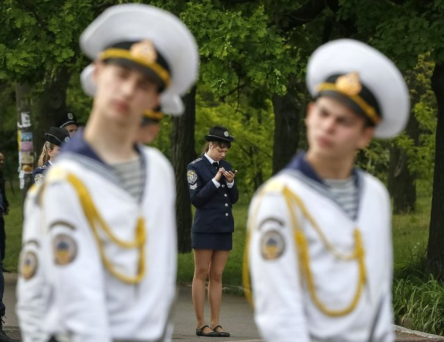 A policewoman uses her mobile phone as navy honor guards stand near of a World War Two memorial during celebrations to mark Victory Day in the Black Sea port of Odessa May 9, 2014. Ukraine celebrates the 1945 victory over Nazi Germany during World War Two on May 9. (Photo by Gleb Garanich/Reuters)