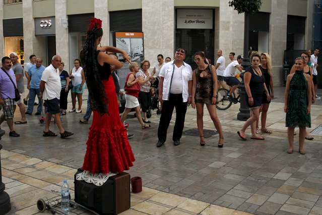 Tourists watch as a woman, wearing a traditional Sevillana dress, performs at Marques de Larios street in downtown Malaga, on Costa del Sol, southern Spain, July 12, 2015. The Spanish government raised the terror-alert level to 4, out of a maximum of 5, after the attacks in France, Tunisia and Kuwait, Spain's Interior Minister Jorge Fernandez Diaz announced on June 26. (Photo by Jon Nazca/Reuters)