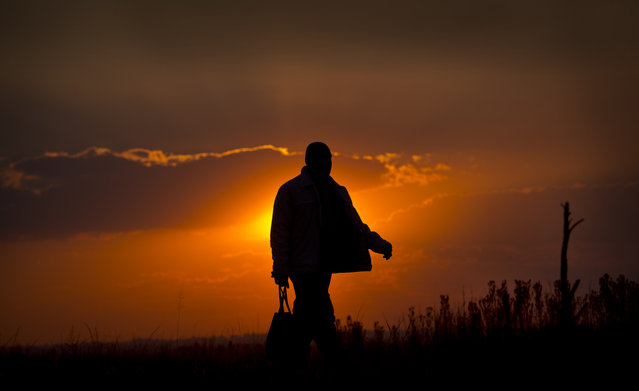 A man walks home at sunset past recently-deployed South African military personnel in the politically-sensitive mining town of Bekkersdal, where there have been recent disputes between supporters of incumbent President Jacob Zuma's African National Congress (ANC) party and supporters of rival Julius Malema's Economic Freedom Fighters (EFF) party, in South Africa Monday, May 5, 2014. (Photo by Ben Curtis/AP Photo)