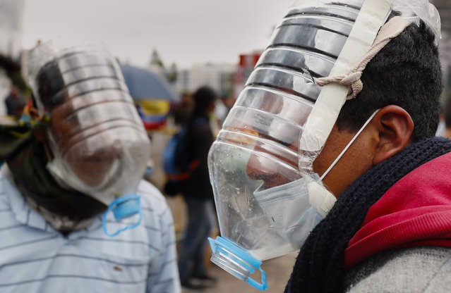 People use homemade gas masks made by Cesar Viteri in Quito, Ecuador, 10 October 2019. Viteri designed his own masks with reused plastic due the need to face tear gases during the clashes in Ecuador's protest. (Photo by Paolo Aguilar/EPA/EFE)