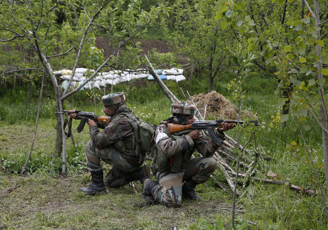 Indian army soldiers take position inside an apple orchard during a search operation in Shopian, about 60 Kilometers south of Srinagar, Indian controlled Kashmir, Thursday, May 4, 2017. Thousands of Indian government forces cordoned off at least two dozen villages in southern Kashmir on Thursday while they hunted for separatist militants believed to be hiding in the area. (Photo by Mukhtar Khan/AP Photo)