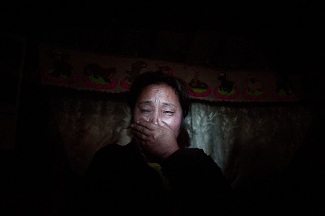 Asia, Mongolia, Ulaan Bator, March 24, 2011. Narantuya Enebish, 45 years old and ex sheperd crying  just after she told me her story. This family lost all of their livestock (100 animals) that was their main source of income during the 2001 Dzud, and they moved from the Tuv province to Ulaan Baator in the Gher District. Her husband was working as taxy driver but after a car crash he is now paralyzed on the bed from 8 years. (Photo by Alessandro Grassani)