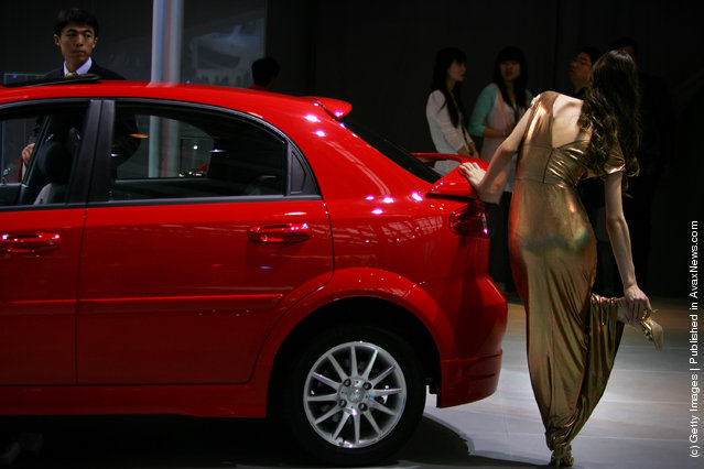 A model relaxes her foot beside the Buick car during a special media opening of the Auto China 2008 show