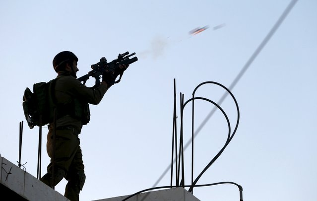 An Israeli soldier fires a tear gas canister towards Palestinian protesters during clashes following a protest against Jewish settlements in the West Bank village of Silwad, near Ramallah July 24, 2015. (Photo by Mohamad Torokman/Reuters)