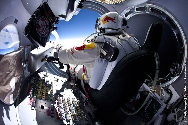 Pilot Felix Baumgartner of Austria prepares to exits the capsule before his jump during the first manned test flight for Red Bull Stratos