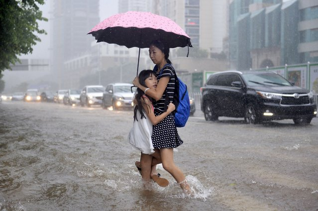A girl clings to her mother as they travel on a flooded street amid heavy rainfall in Shenzhen, Guangdong province, China, July 24, 2015. Approximately a million people have been affected by severe downpours in several Chinese provinces, causing collapsed houses, decimating crops as well as blocking highways, reported Xinhua News Agency. (Photo by Reuters/Stringer)