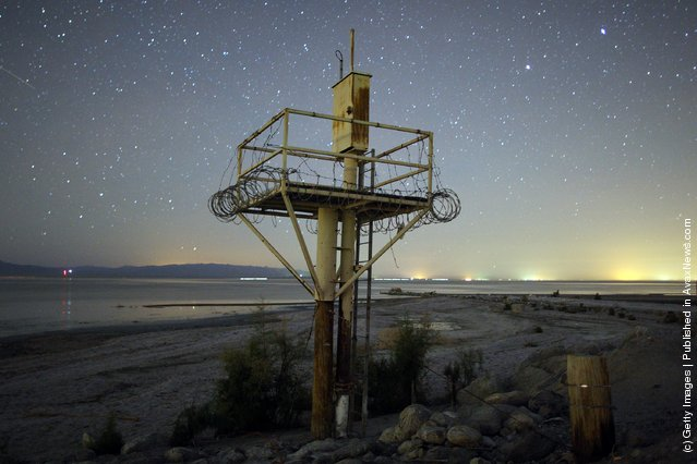 Stars are seen in abundance over a disused structure, on the shore of the Salton Sea