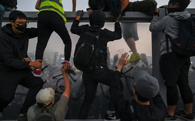 """Pro-democracy protesters climb over a highway dividers fleeing from police arrests during a mass rally on December 1, 2019 in Hong Kong, China. Anti-government protests in Hong Kong stretched into its sixth month after scoring a major victory in the District Council elections as pro-democracy demonstrators continue their demands for an independent inquiry into police brutality, the retraction of the word """"riot"""" to describe the rallies, and genuine universal suffrage. (Photo by Billy H.C. Kwok/Getty Images)"""