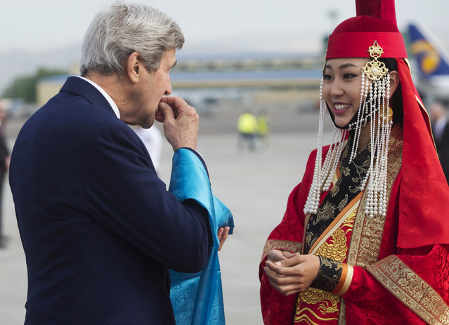 U.S. Secretary of State John Kerry samples cheese curds presented by a woman in traditional attire (R) upon his arrival at Chinggis Khaan International Airport in Ulaanbaatar, Mongolia, June 5, 2016. (Photo by Saul Loeb/Reuters)