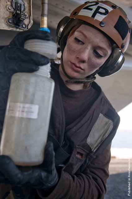 Aviation Ordnanceman Airman Samantha Phillips collects fuel samples from an F/A-18E Super Hornet from the Black Aces of Strike Fighter Squadron (VFA) 14 on the flight deck of the Nimitz-class aircraft carrier USS John C. Stennis (CVN 74)