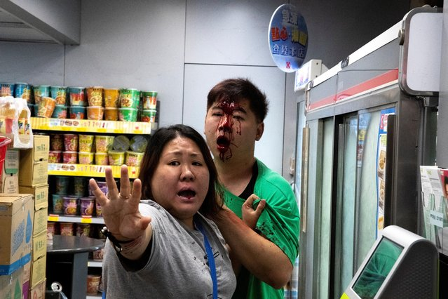 A woman tries to stop anti-government protesters as they attack a man during a protest at Tseung Kwan O district, in Hong Kong, October 13, 2019. (Photo by Athit Perawongmetha/Reuters)