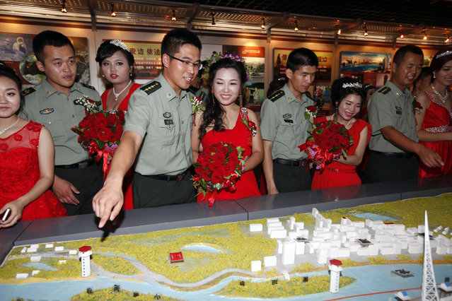 Chinese People's Liberation Army (PLA) officers look over a map of their military positions with their brides after a mass wedding for 14 military couples in Heihe in northeastern China's Heilongjiang province Saturday, August 1, 2015. Saturday is Army Day in China, a holiday commemorating the establishment of the PLA. (Photo by Chinatopix Via AP Photo)
