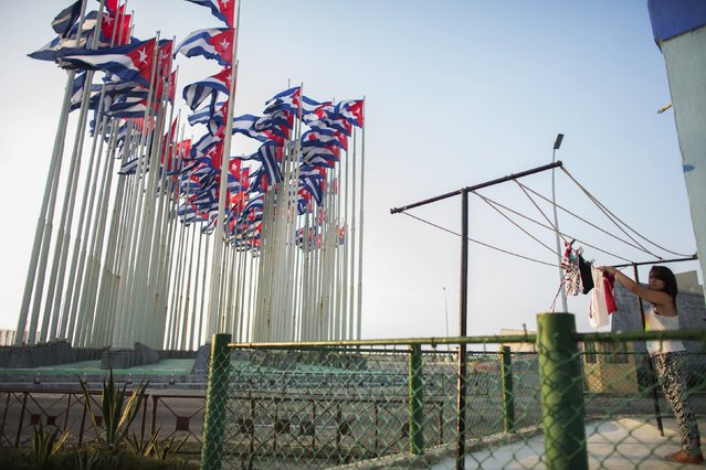 A woman hangs clothes near Cubans flags flying in front of the U.S embassy, in Havana, July 27, 2015. U.S. Secretary of State John Kerry will travel to Cuba on August 14 to formally re-designate the U.S. Interests Section as the U.S. Embassy in Havana. (Photo by Alexandre Meneghini/Reuters)