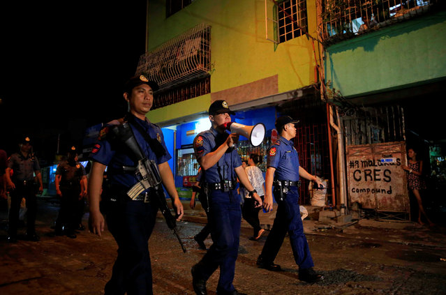 """A member of the Philippine National Police uses a megaphone to advise residents of their operation, """"Rid the Streets of Drinkers and Youth"""" during a foot patrol along a main street of  Las Pinas city, south of Manila, Philippines June 10, 2016. (Photo by Romeo Ranoco/Reuters)"""